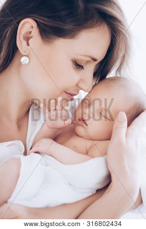 Stock Photo - Portrait of a cute little baby girl  is in the arms of her mother