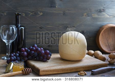 Round Head Of Cheese Kostromskoy On Textured Dark Wooden Background On Square Plate With Grapes, Hon