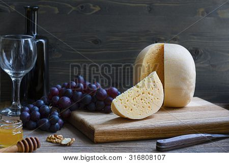 Round Head Of Cheese Kostromskoy With Cut Piece On Wooden Background On Square Plate With Grapes, Ho