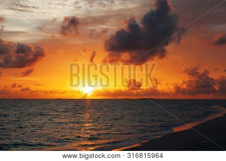 Beautifull red golden sunset. Colorful dawn over the sea. Nature beauty. Enjoying the sundawn with cloudy sky on the beach.