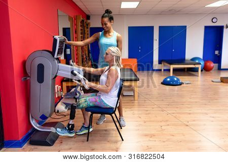 Side view of African-american female trainer assisting disabled Caucasian active senior woman to exercise in exercise equipment at sports center. Sports Rehab Centre with physiotherapists and patients