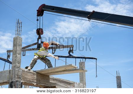 Construction Workers Control The Spread Of Concrete Slabs In The Construction Area And The Bright Bl