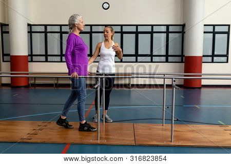 Side view of female physiotherapist helping disabled senior woman walk with parallel bars in sports center. Sports Rehab Centre with physiotherapists and patients working together towards healing