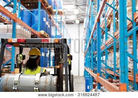 Rear view of female staff driving forklift in warehouse. This is a freight transportation and distribution warehouse. Industrial and industrial workers concept