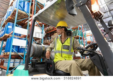 Low angle view of female staff driving forklift in warehouse. This is a freight transportation and distribution warehouse. Industrial and industrial workers concept
