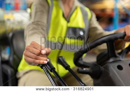Close-up of female staff driving forklift in warehouse. This is a freight transportation and distribution warehouse. Industrial and industrial workers concept