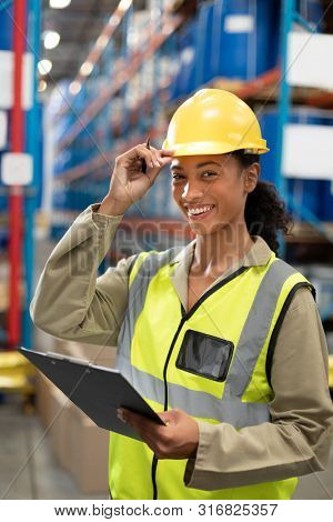 Happy female staff looking at camera while holding clipboard in warehouse. This is a freight transportation and distribution warehouse. Industrial and industrial workers concept