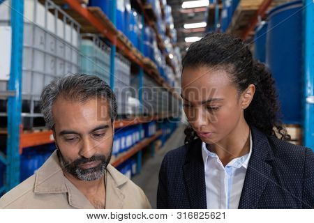 Close-up of female manager and male worker standing together in warehouse. This is a freight transportation and distribution warehouse. Industrial and industrial workers concept