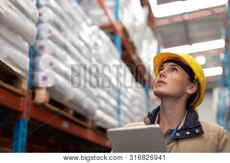 Low angle view of female worker with digital tablet looking up in warehouse. This is a freight transportation and distribution warehouse. Industrial and industrial workers concept