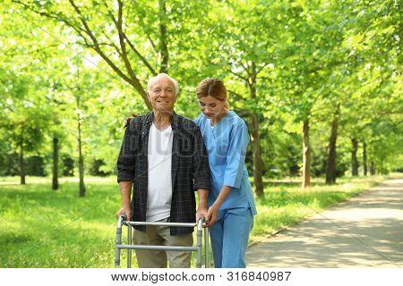 Happy Nurse Assisting Elderly Man With Walking Frame At Park