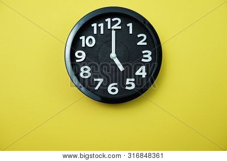 Black Round Clock Showing Five O'clock On Yellow Background