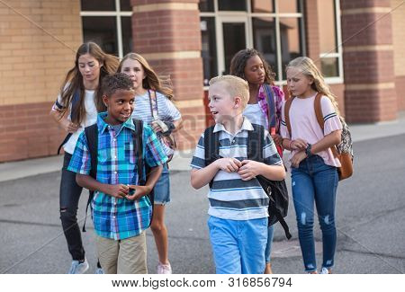 Large, diverse group of kids leaving school at the end of the day. School friends walking together and talking together on their way home