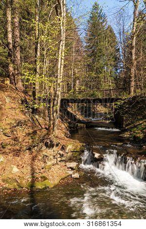 Blatny Potok Creek Above Moravka Village With Small Water Cascades, Bridge Above, Trees Around And C