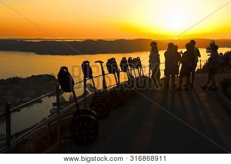 Bergen, Norway - July 25, 2019: Beautiful Landscape, Group Of Tourists, Segways And Sunset Seen From