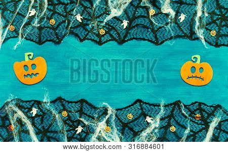 Halloween card.Halloween background with spider web, spiders and smiling jack decorations as symbols of Halloween on the dark green wooden background. Halloween concept