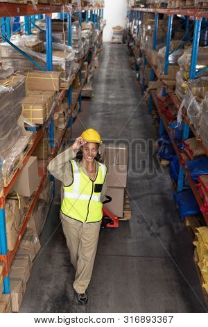 High angle view of female worker carrying cardboard boxes on pallet jack in warehouse. This is a freight transportation and distribution warehouse. Industrial and industrial workers concept