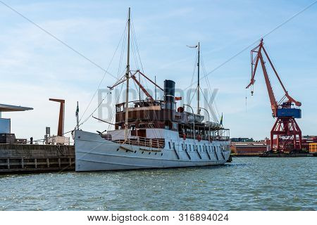 Summer Seascape View Of An Old Moored Steamboat Ship In The Harbor With Cranes In The Background In