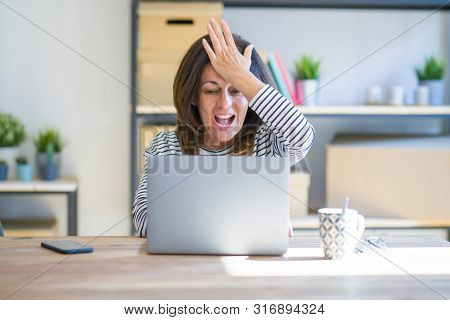 Middle age senior woman sitting at the table at home working using computer laptop surprised with hand on head for mistake, remember error. Forgot, bad memory concept.