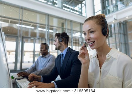 Close up of a young Caucasian woman in a call centre sitting at a computer and speaking into her headset. In the background a young Caucasian man and a young African American man are also sitting at