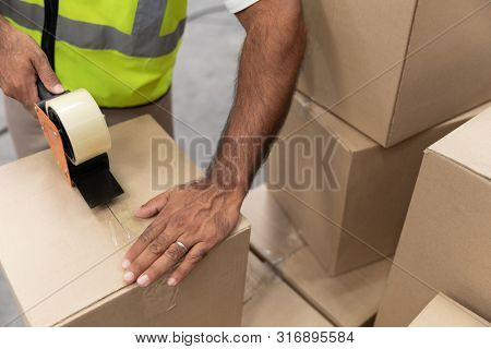 Close-up of male worker packing cardboard box with tape gun dispenser in warehouse. This is a freight transportation and distribution warehouse. Industrial and industrial workers concept