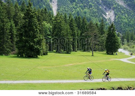 Distant Cyclists On Mountain Lakeside