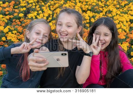 Russia, Kazan - August 8, 2019: Three Teen Girls Take A Selfie On Iphone Xs On A Sunny Day And Laugh