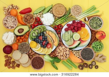 Vegan health food for a healthy life concept with a large super food collection. Healthy foods high in protein, omega 3, antioxidants, anthocyanins, vitamins & dietary fibre. Top view on yellow wood.