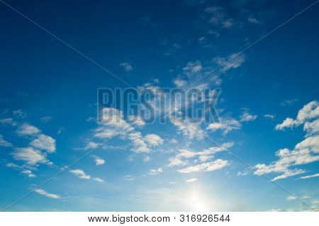 Blue dramatic sky background - white dramatic colorful clouds lit by sunlight. Vast sky landscape panoramic scene, colorful sky landscape, sky nature scene