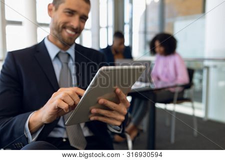 Close up of young Caucasian businessman using a tablet computer sitting in an office. The focus is on his hands and the tablet. Two colleagues work siting at desk in the background. Modern corporate
