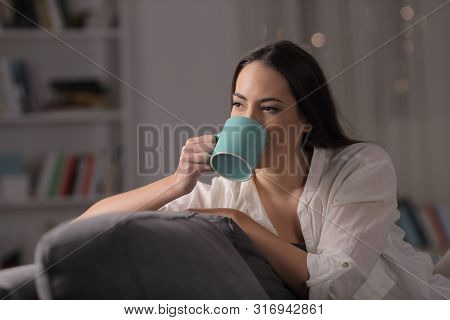 Lady Drinking Coffee Sitting On A Couch In The Night At Home