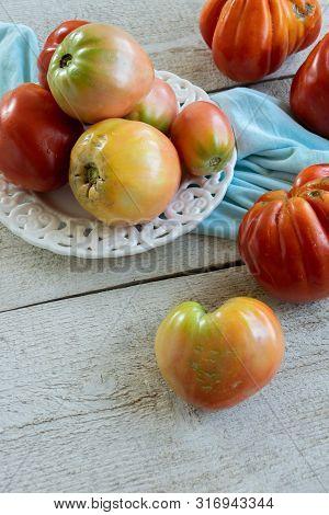 Raw Ripe Graden Tomatoes On Wooden Background. Vegetarian Ingredients, Seasonal Produce