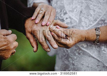 Elder Couples Hands Put On The Wedding Rings On Each Other. Elderly Couple Wedding.gold Couple Is Ge