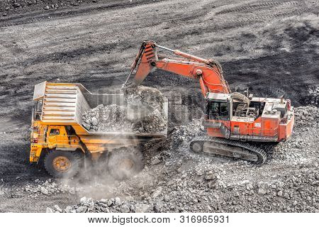 Coal Mining In A Quarry. A Hydraulic Excavator Loads A Dump Truck. Loading Of Coal Into The Body Of