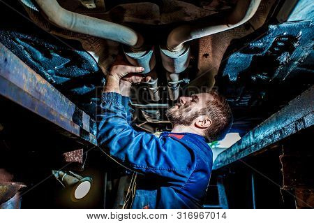 Handsome Mechanic In Uniform Are Working In Auto Service With Lifted Vehicle. Car Repair And Mainten