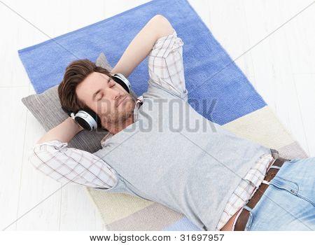 gut aussehend junger Mann mit Stock, hören Musik über Kopfhörer mit geschlossenen Augen.