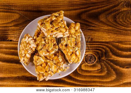 Ceramic Plate With Peanut Brittles On Rustic Wooden Table. Top View