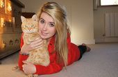 Pretty teen wearing red laying on the floor cuddling her ginger cat poster