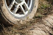 Dirty 4x4 SUV car wheel with light alloy disc is on rural roadside with grass, close up photo, off-road racing theme poster