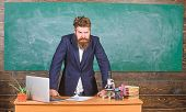Teacher interesting interlocutor as authority. Teacher bearded man tell scary story. Talking to students or pupils. Teacher charismatic hipster stand near table classroom chalkboard background poster