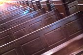 Cathedral pews. Rows of benches in christian church. Heavy solid uncomfortable wooden seats. poster
