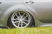 tuned alloy wheels with a wide rim on an lowered silver car standing on the grass. poster