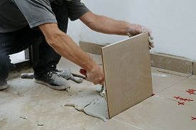 Gluing Tiles On The Floor. Laying Tiles On The Floor.  Worker Installing Ceramic Tiles On The Floor