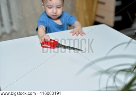 Danger In The Home, Sharp Objects Are Dangerous For Young Children. Little Boy Picks Up Scissors Fro