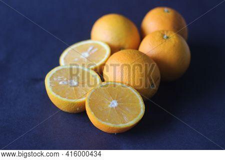 Kinnows And Sliced Kinnows Which Looks Like Orange.