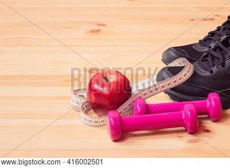 Dumbbells, Measuring Tape, Apple And Sneakers. Selective Focus. Fitness, Healthy And Active Lifestyl