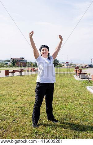 Happy Senior Woman In Sports Clothes Exercising In The Park Standing With Arms Up