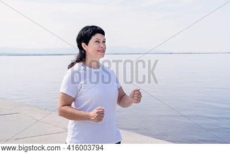 Active Senior Woman Jogging Near The Riverside