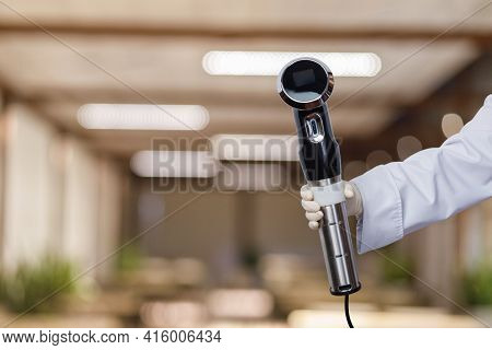 The Chef Shows An Apparatus For Working On Sous Vide Technology On A Blurred Background Of The Resta