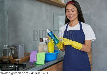 Joyful Young Woman, Cleaning Lady Wearing Protective Gloves, Smiling And Holding Household Cleaning