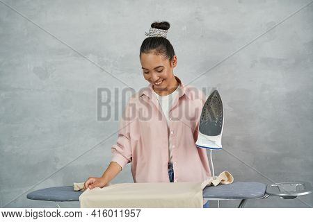 Fresh And Ironed. Attractive Young Woman Smiling While Ironing Clothes On Ironing Board At Home